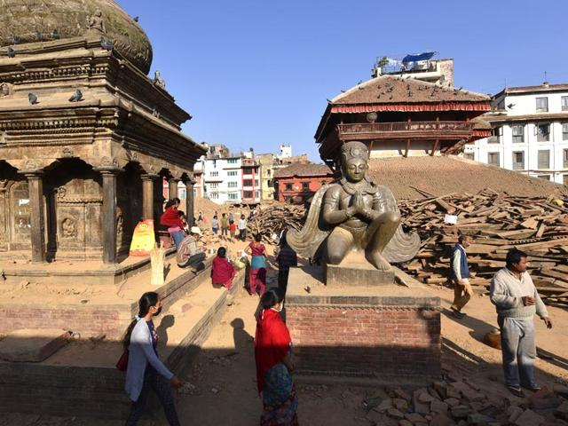 A statue of King Pratap Malla in a praying posture flanked by the devastation caused by the killer temblor, in Kathmandu. (Gurinder Osan/HT Photo)