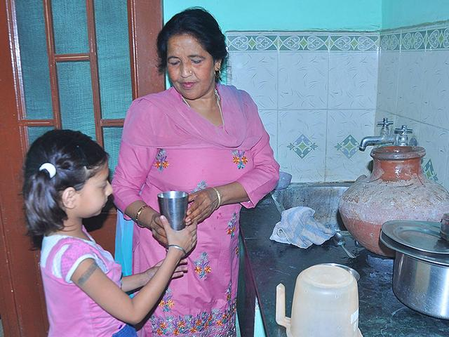 A-member-of-the-staff-offering-a-glass-of-water-to-a-girl-at-a-creche-in-Mani-Majra-Sant-Arora-HT-Photo