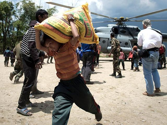 A-Nepalese-boy-carrying-a-bag-of-rice-out-of-an-IAF-helicopter-bringing-relief-food-to-the-village-of-Barpak-nine-days-after-a-devastating-earthquake-struck-the-Himalayan-nation-on-April-25-AFP-Photo