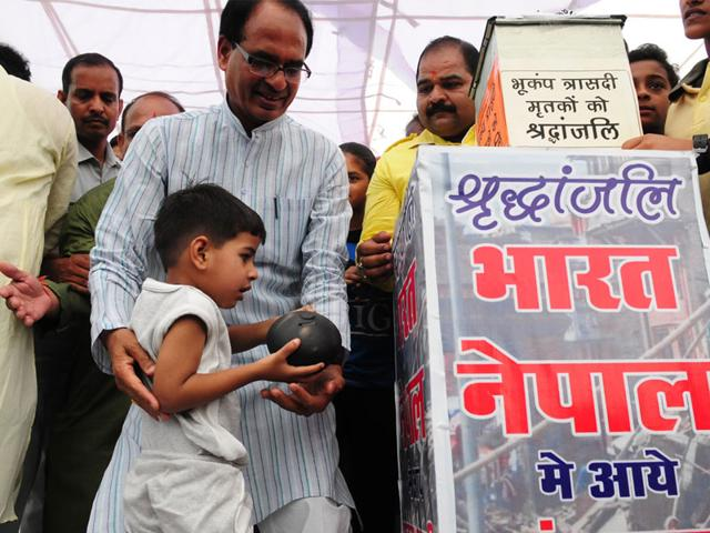 Three-year-old-Prateek-Soni-hands-over-his-piggy-bank-savings-to-chief-minister-Shivraj-Singh-Chouhan-for-Nepal-quake-victims-in-Bhopal-Tuesday-Mujeeb-Faruqui-HT-photo