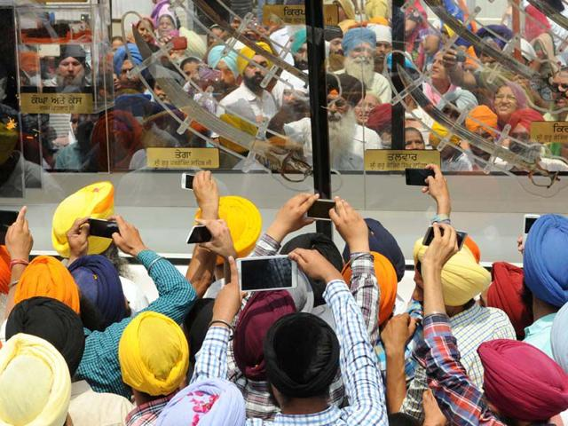 Devotees-taking-pictures-of-Guru-Gobind-Singh-s-relics-during-a-religious--procession-in-Patiala-on-Wednesday-Bharat-Bhushan-HT