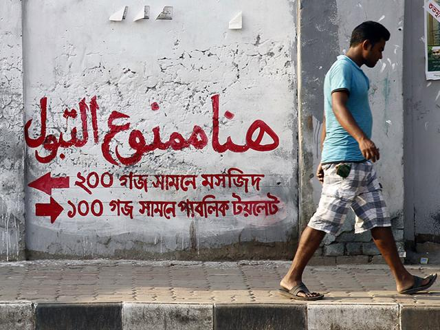 A-pedestrian-walks-past-a-message-written-on-a-wall-in-Arabic-which-states-Do-not-urinate-here-in-Dhaka-AFP-Photo
