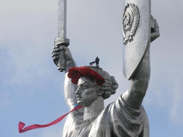A-worker-installing-a-wreath-of-poppies-as-a-red-peak-and-ribbon-on-top-of-the-102-meter-Motherland-Monument-in-Kiev-to-mark-the-anniversary-of-the-defeat-of-the-Nazis-in-WWII-AP-Photo