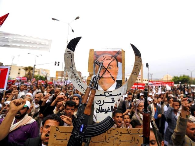 Houthi-followers-hold-up-a-defaced-poster-of-Yemeni-President-Abd-Rabbu-Mansour-Hadi-during-a-demonstration-against-the-Saudi-led-air-strikes-in-Sanaa-Reuters-Khaled-Abdullah
