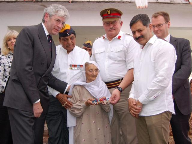 Naik-Kirpa-Ram-s-widow-Brahmi-Devi-holding-the-George-Cross-as-Brig-Brian-McCall-third-from-right-defence-adviser-at-the-British-High-Commission-in-India-and-British-lawyer-Ian-Mayes-left-look-on-during-a-function-at-Bhapral-village-in-Bilaspur-district-on-Monday-HT-Photo