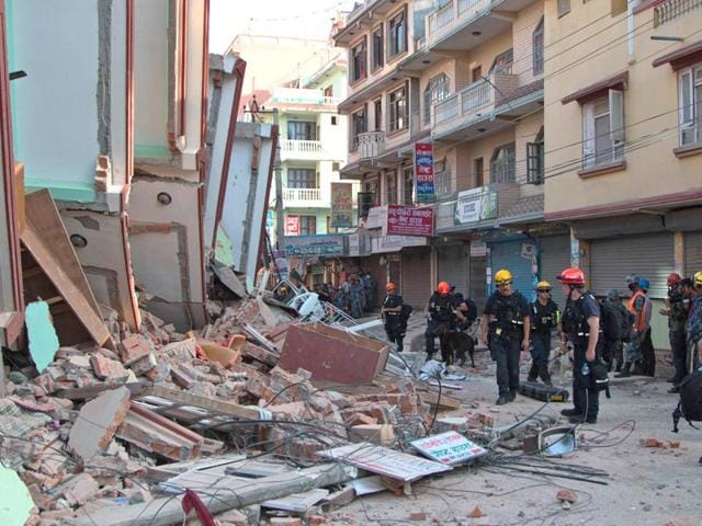 People-walk-along-the-debris-of-collapsed-houses-after-a-fresh-7-3-magnitude-earthquake-in-Nepal-Reuters-Photo