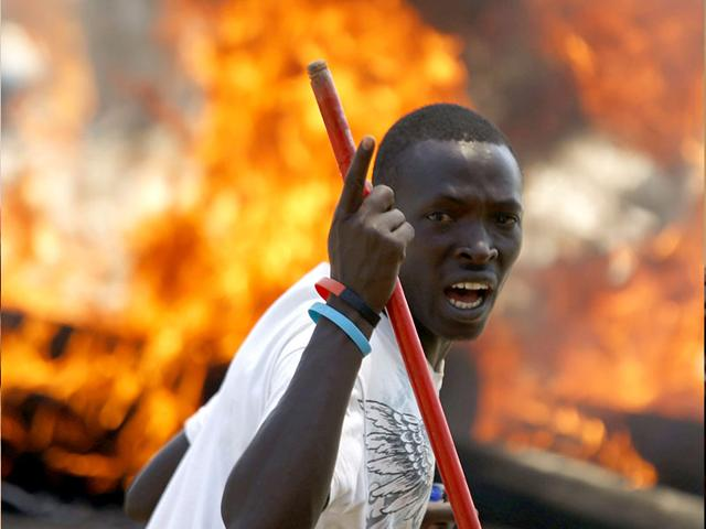A-protester-stands-in-front-of-a-burned-barricade-during-a-protest-against-Burundian-President-Pierre-Nkurunziza-s-decision-to-run-for-a-third-term-in-Bujumbura-Burundi--Reuters