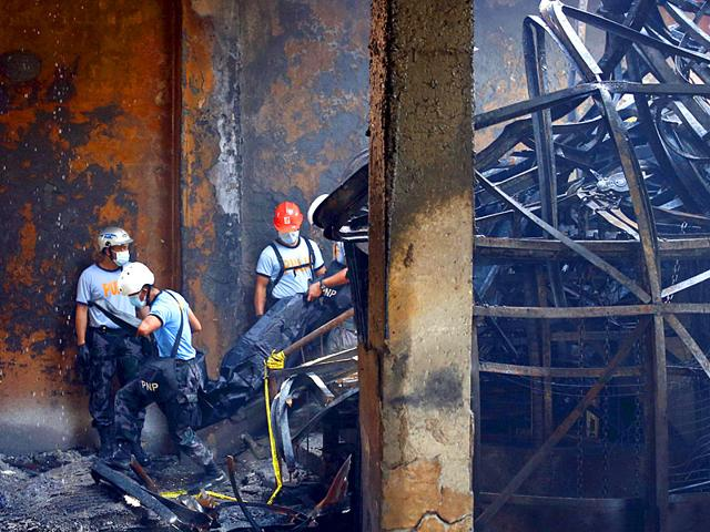 Police-carry-a-body-bag-containing-a-body-of-a-worker-amidst-debris-inside-a-gutted-slipper-factory-in-Valenzuela-Metro-Manila-in-the-Philippines-Reuters