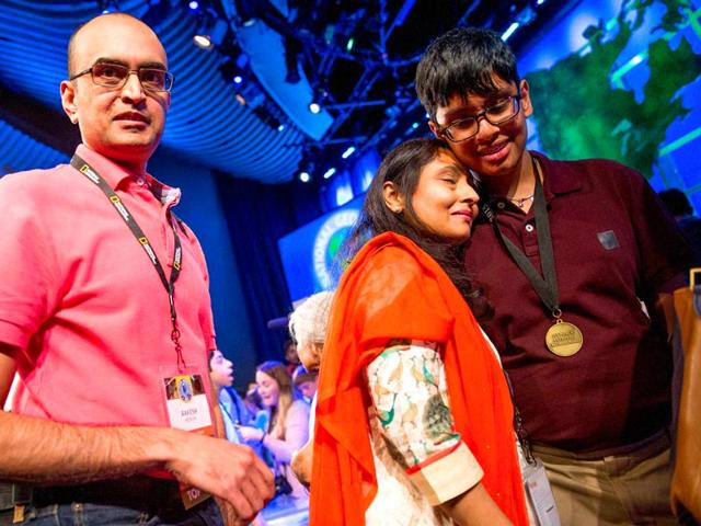 Karan-Menon-of-New-Jersey-right-is-greeted-on-stage-by-his-parents-Rakesh-and-Manisha-after-he-won-the-National-Geographic-Bee-competition-AP-Photo