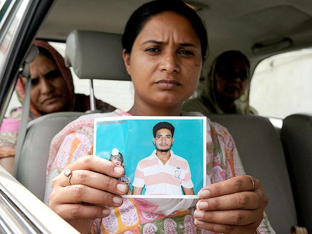 Gurpinder-Kaur-showing-a-photo-of-her-missing-brother-HT-Photo