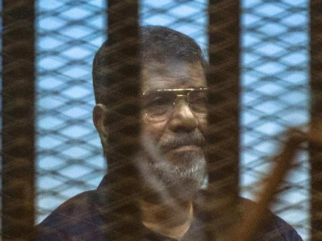 Egypt-s-deposed-Islamist-president-Mohammed-Morsi-sits-behind-the-defendant-s-cage-as-the-judge-reads-out-his-verdict-sentencing-him-and-more-than-100-other-defendants-to-death-at-the-police-academy-in-Cairo-AFP-Photo