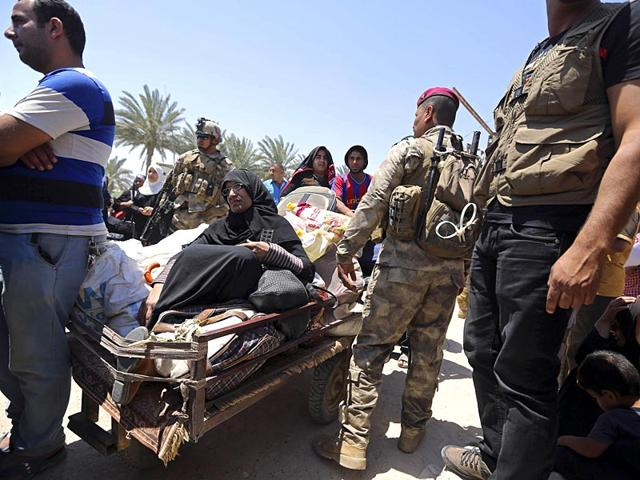 Iraqi-security-forces-guard-displaced-Iraqis-from-Ramadi-as-they-cross-the-Bzebiz-bridge-after-spending-the-night-walking-towards-Baghdad-as-they-flee-their-hometown-65km-west-of-Baghdad-AP-Photo