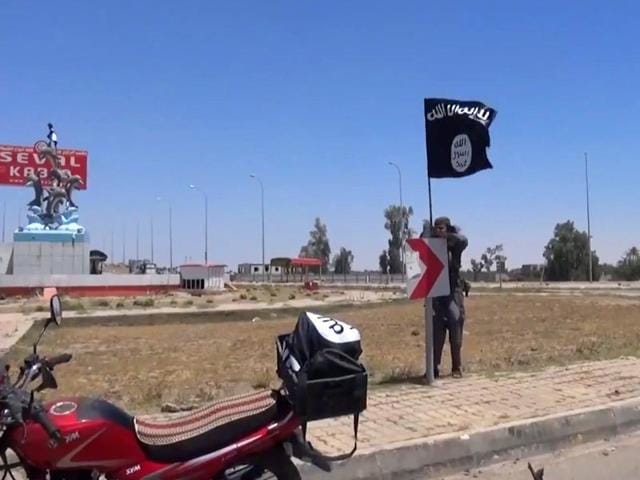 An-image-grab-taken-from-a-video-uploaded-on-May-18-2015-by-Aamaq-News-Agency-a-Youtube-channel-which-posts-videos-from-areas-under-the-Islamic-State-IS-group-s-control-allegedly-shows-an-IS-fighter-hanging-a-flag-of-the-group-in-a-street-of-Ramadi-AFP-Photo