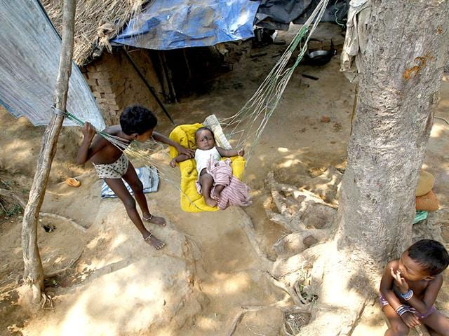 An-impoverished-girl-swings-her-baby-brother-in-a-makeshift-hammock-in-Bhubaneswar-The-first-year-of-Narendra-Modi-s-government-has-seen-cutbacks-in-welfare-programmes-for-the-poor-say-activists-AP-Photo