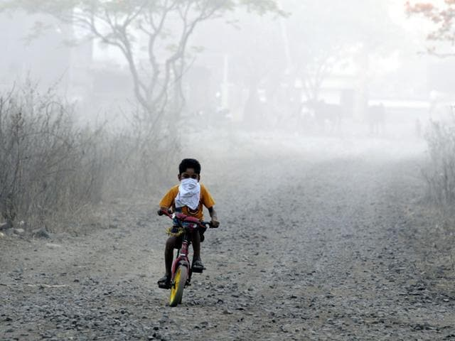 A-child-cycles-near-the-Devguradiya-trenching-ground-with-his-face-covered-to-protect-him-from-the-smoke-and-poisonous-gases-Schools-and-colonies-located-within-3-4-kms-from-the-trenching-ground-are-severely-affected-by-toxic-material-sent-into-the-air-and-groundwater-Shankar-Mourya-HT-photo