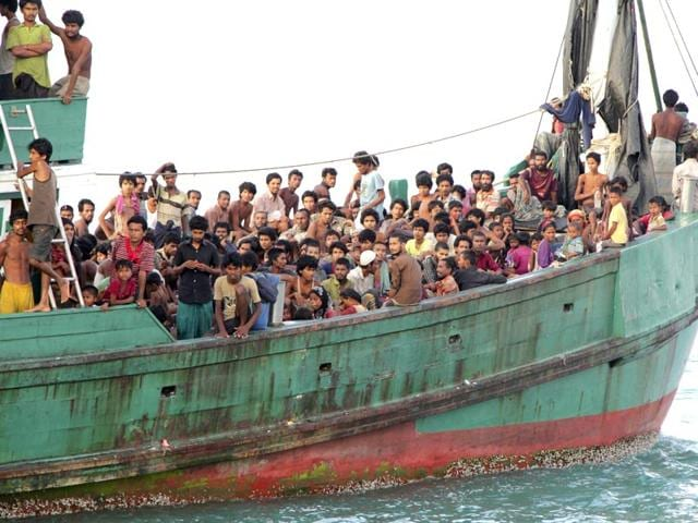 In-this-file-photo-migrants-sit-on-their-boat-as-they-wait-to-be-rescued-by-Acehnese-fishermen-on-the-sea-off-East-Aceh-Indonesia-Many-of-the-thousands-of-migrants-abandoned-at-sea-in-Southeast-Asia-this-month-are-Rohingya-Muslims-who-fled-their-home-country-of-Myanmar-AP-Photo
