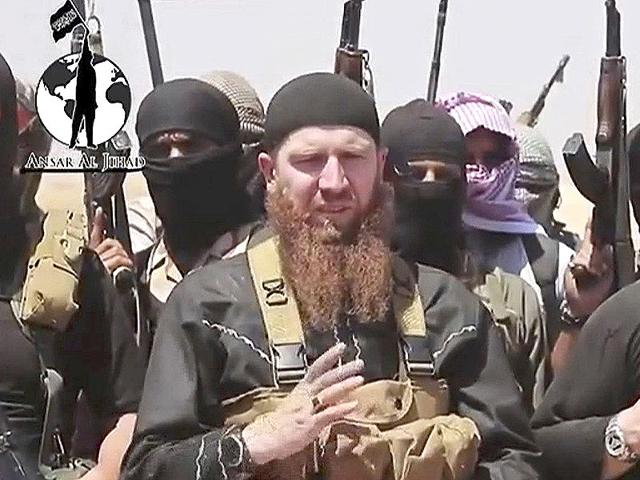 This-image-made-from-an-undated-video-on-a-social-media-account-frequently-used-for-communications-by-the-Islamic-State-shows-Omar-al-Shishani-standing-next-to-the-group-s-spokesperson-among-a-group-of-fighters-as-they-declare-the-elimination-of-the-border-between-Iraq-and-Syria-Militant-social-media-account-via-AP