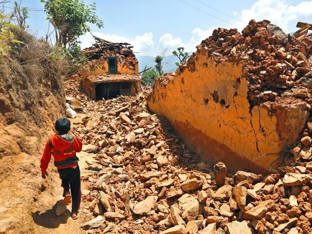 A-Nepalese-boy-runs-past-houses-destroyed-in-the-April-25-earthquake-in-Pauwathok-village-Sindhupalchok-district-Nepal-AP-Photo