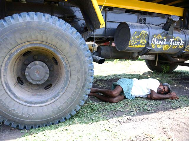 A-man-rests-under-a-transport-vehicle-on-the-outskirts-of-Hyderabad-AFP-Photo