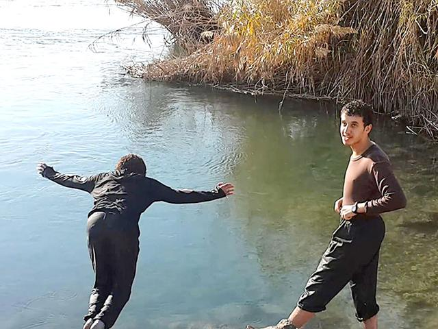 File-photograph-of-two-members-of-the-Islamic-State-group-spend-time-at-the-Euphrates-river-in-Raqqa-Syria-Helping-fighters-marry-whether-Syrians-or-foreigners-is-a-key-priority-for-the-Islamic-State-group-Militant-website-via-AP