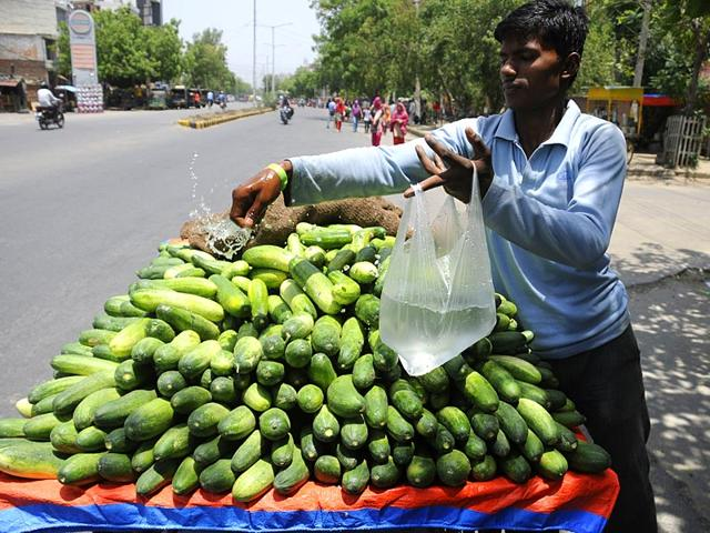 A street vendor spraying water at cucumber in hot weather for the freshness in Noida. The city has recorded a temperature of more than 42 degrees. (Parveen Kumar/HT Photo)