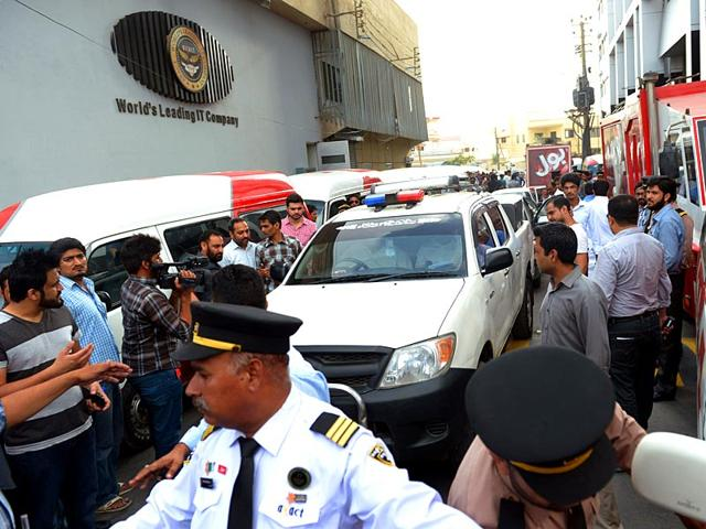 People-gather-at-the-entrance-of-the-Axact-company-building-after-a-raid-by-the-Federal-Investigation-Agency-FIA-in-Rawalpindi-on-May-19-2015-AFP-Photo