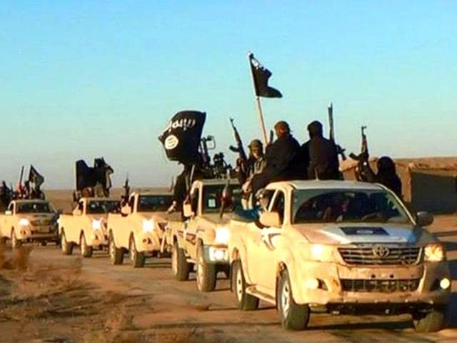 In-this-undated-photo-released-by-a-militant-website-militants-of-the-Islamic-State-group-hold-up-their-weapons-and-wave-its-flags-on-their-vehicles-in-a-convoy-on-a-road-leading-to-Iraq-while-riding-in-Raqqa-city-in-Syria-Militant-website-via-AP