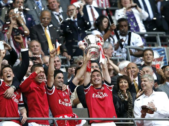 Arsenal-players-hold-the-trophy-as-they-celebrate-winning-the-English-FA-Cup-final-match-against-Hull-City-at-Wembley-Stadium-in-London-on-May-17-2014-AFP-Photo