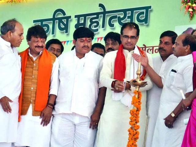 Chief-minister-Shivraj-Singh-Chouhan-flanked-by-ministers-and-party-leaders-lights-a-traditional-lamp-to-inaugurate-Krishi-Mahotsava-in-Ujjain-on-Friday-HT-photo