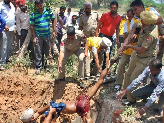 A-rescue-team-pulling-out-the-body-of-a-worker-from-the-sewer-in-Sector-31-Chandigarh-and-right-the-victims-Karun-Sharma-HT-Photo