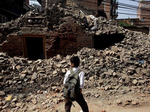 A-Nepalese-boy-walks-past-a-collapsed-building-close-to-his-school-AP-Photo