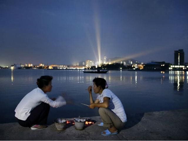 North-Korean-women-talk-on-a-pier-leading-to-Jangdok-Island-at-dusk-in-Wonsan-North-Korea-AP-File-Photo