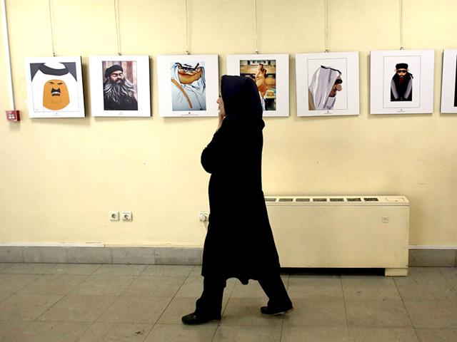 An-Iranian-woman-walks-past-cartoons-displayed-during-an-exhibition-as-part-of-the-anti-IS-cartoon-contest-at-Arasbaran-gallery-in-Tehran-AFP-Photo