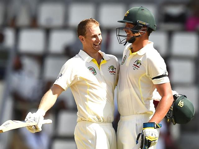 Australia-s-Adam-Voges-L-celebrates-with-teammate-Josh-Hazlewood-after-scoring-his-100th-run-during-play-on-the-second-day-of-the-first-cricket-Test-match-between-Australia-and-the-West-Indies-at-Windsor-Park-Stadium-in-Roseau-Dominica-AFP-Photo