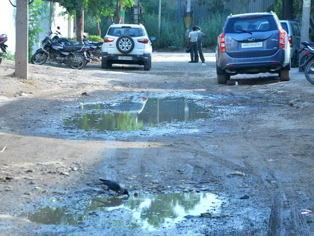 Commuters-having-a-bumpy-ride-on-the-road-filled-with-potholes-Sant-Arora-HT-Photo