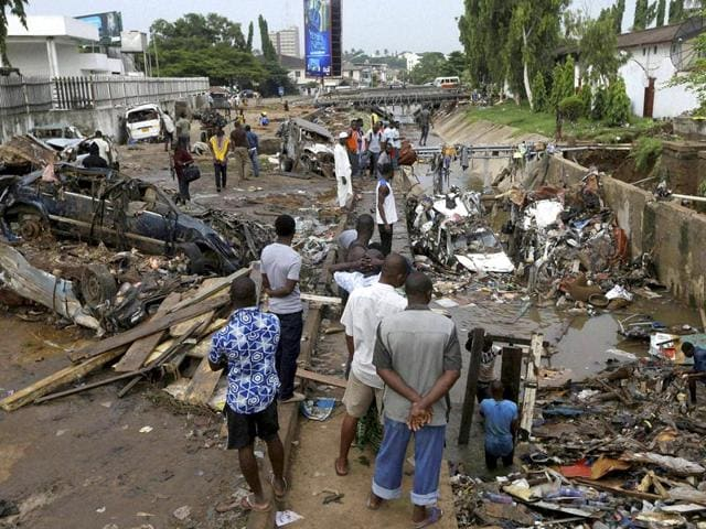 People-gather-around-destroyed-cars-swept-into-a-gully-by-flash-floods-in-Ghana-AP-Photo
