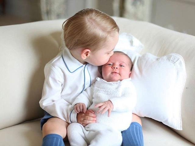 First photos of Britain's princess show kiss from little big brother