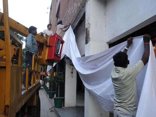 Workers-deployed-by-the-Estate-Office-breaking-the-glass-of-a-window-and-left-glow-signboards-being-removed-during-the-drive-in-Sector-17-E-in-Chandigarh-on-Monday-Karun-Sharma-HT