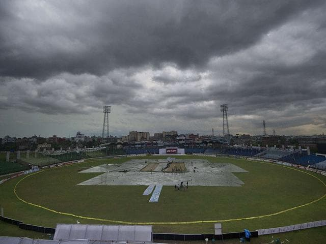Ground-staff-cover-the-playing-field-during-the-rain-interrupted-Test-between-Bangladesh-and-India-at-Fatullah-on-June-11-2015-AFP-Photo