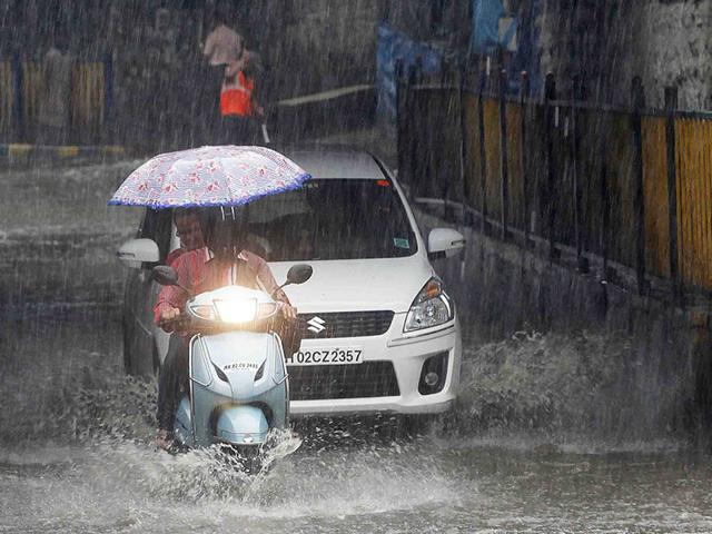 Workers-of-an-electronic-showroom-drain-out-rainwater-logged-inside-the-showroom-in-Bhopal-on-Tuesday-Mujeeb-Faruqui-HT-photo