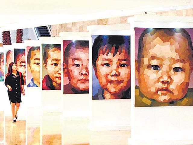 A-woman-stands-in-front-of-a-portrait-of-a-missing-child-during-an-exhibition-at-a-square-in-Nanjing-Jiangsu-province-REUTERS