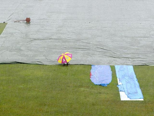Ground-staff-cross-the-covered-field-as-rain-interrupts-play-during-the-one-off-Test-match-between-Bangladesh-and-India-at-Fatullah-on-June-13-2015-AFP-Photo