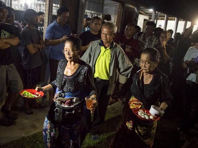 Spirit-mediums-dip-one-of-the-ritual-relic-in-chicken-blood-during-an-ancient-ritual-at-village-community-hall-in-Tuaran-in-eastern-Sabah-state-on-Borneo-island-Malaysia-AP-Photo