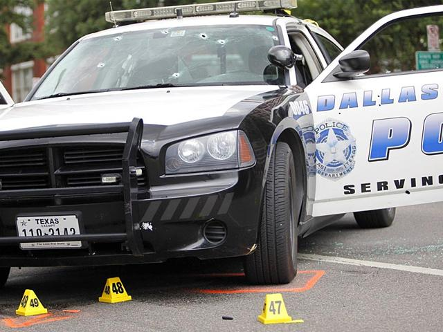 Evidence-markers-are-placed-around-a-Dallas-Police-vehicle-riddled-with-bullet-holes-from-the-attack-on-June-13-AFP-Photo