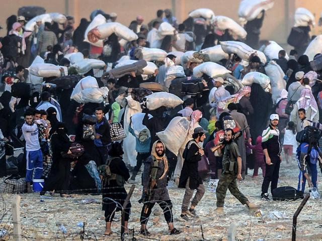 Syrian-refugees-run-away-as-Turkish-soldiers-use-water-cannons-to-move-them-away-from-fences-at-the-Turkish-border-near-the-Syrian-town-of-Tal-Abyad-AFP-Photo
