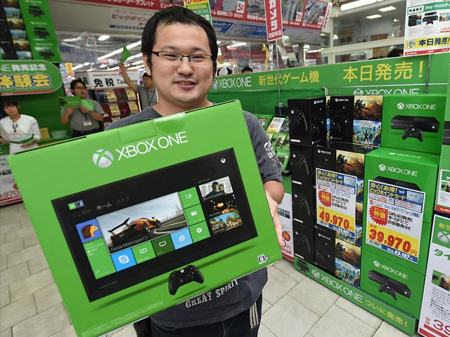 A-customer-holds-a-box-containing-Microsoft-s-video-game-console-Xbox-One-at-a-household-appliance-shop-in-Tokyo-Photo-AFP
