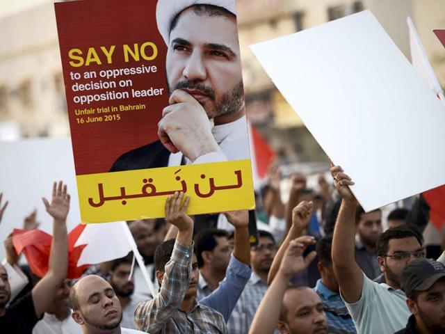 Bahraini-protesters-hold-a-placard-portraying-Sheikh-Ali-Salman-head-of-the-Shiite-opposition-movement-Al-Wefaq-during-a-demonstration-against-his-arrest-AFP-Photo