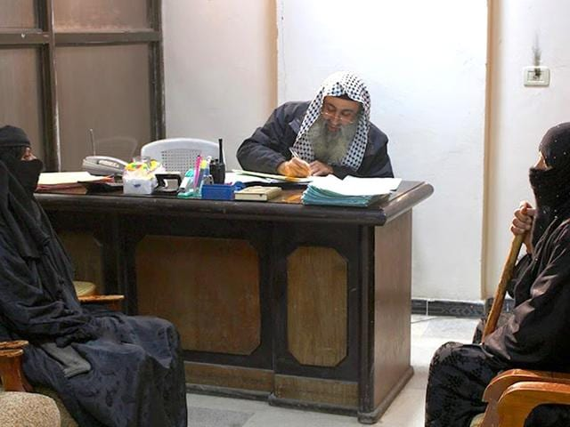 In-this-photo-released-by-a-militant-website-which-has-been-verified-and-is-consistent-with-other-AP-reporting-two-women-sit-in-the-office-of-an-Islamic-State-group-judge-at-an-Islamic-court-in-al-Tabqa-town-in-Raqqa-City-Syria-Militant-website-via-AP