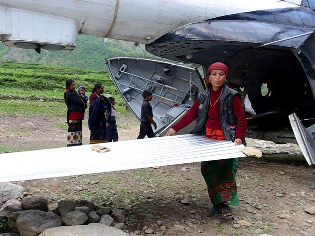 Nepalese-villagers-unloading-a-zinc-sheet-as-relief-material-arrives-by-helicopter-in-the-village-of-Sirdibas-in-Gorkha-District-some-250kms-north-west-of-Kathmandu-AFP-photo