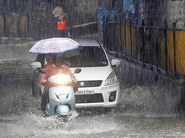 A-vehicle-stuck-in-rain-water-at-a-road-as-boys-having-fun-after-heavy-shower-in-Mumbai-PTI-Photo
